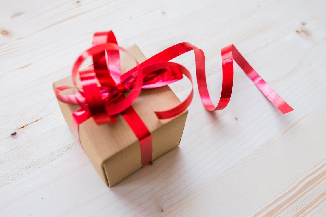 brown paper wrapped gift with curly red bow