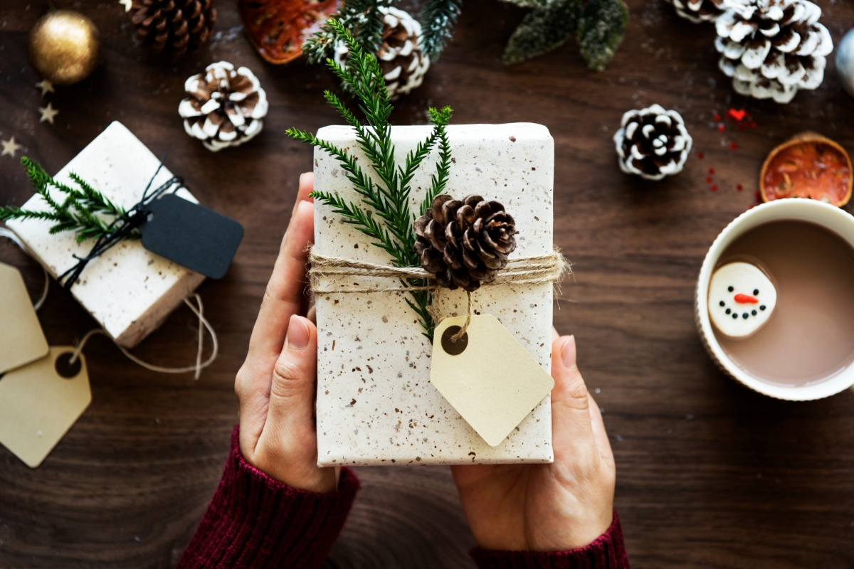 person holding a holiday gift wrapped and decorated with a pinecone