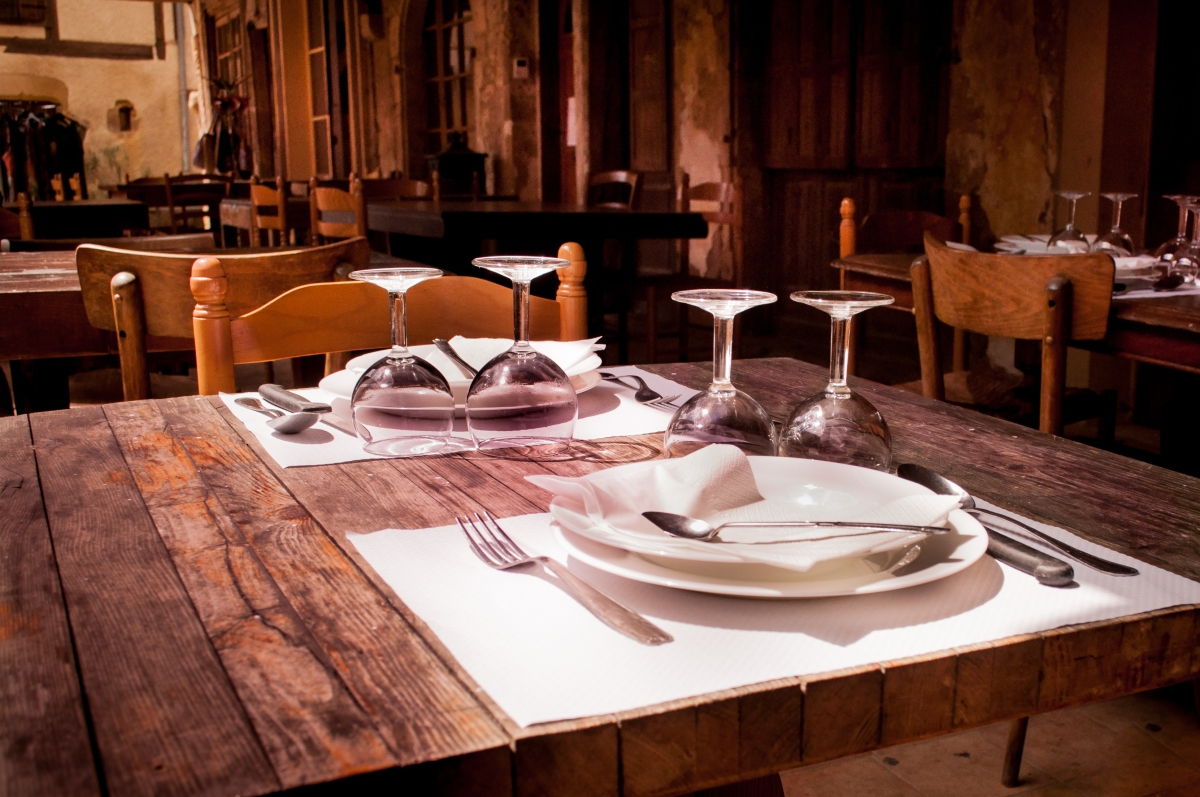 Wood dining table in a restaurant set with dishes and wine glasses