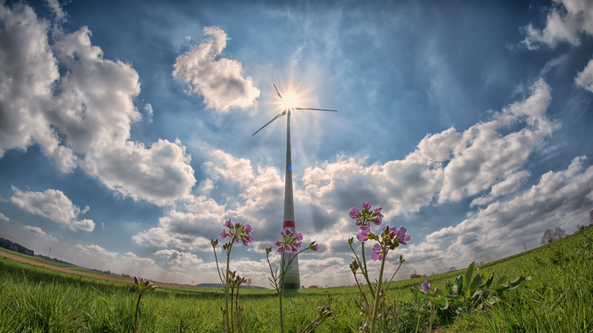 a scenic image of a wind turbine in a green field with clouds and blue sky
